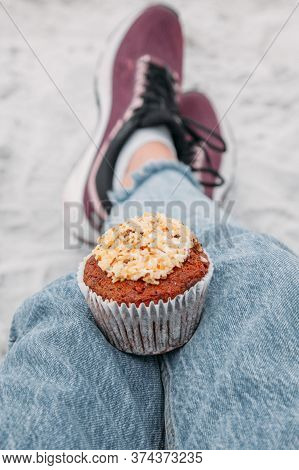 Girl Holds A Delicious Muffin (cupcake) Cake With Cream And Nuts During A Picnic On The Beach. The C