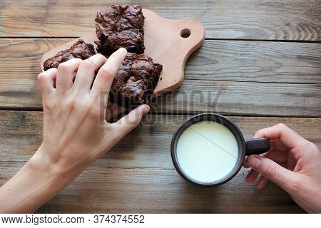 Woman Hands Holding A Cup Of Milk And Taking A Chocolate Cake With Cherries. Eating At Home Concept.