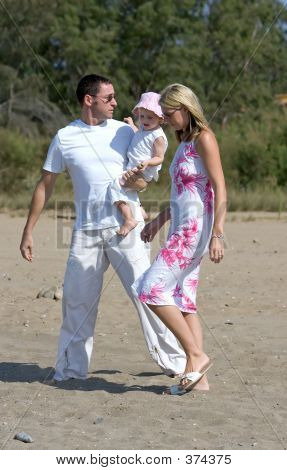 Young, Healthy Family Walking Along A Sunny Beach