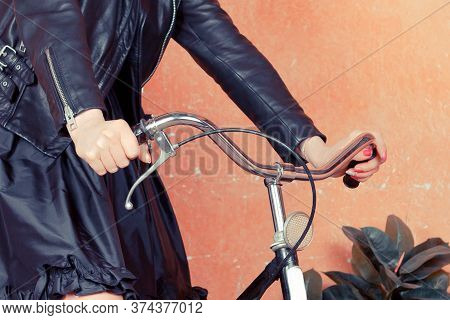 The Girl Is A Cyclist In A Black Leather Jacket And Skirt Behind The Wheel Of A Retro Bike, Handbrak