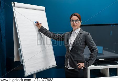 Friendly Woman In A Suit Writes On A Blank White Board With A Marker. Red-haired Girl Makes A Presen