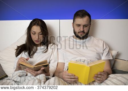 Beautiful Young Couple Sitting In Bed Reading Books At Home In Bedroom, Smart Girl And Guy Resting B