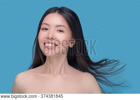 Smiling Young Dark-haired Woman With Fluttering Hair