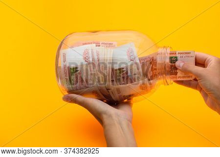 Hands Pull A Five Thousandth Bill Out Of A Glass Jar
