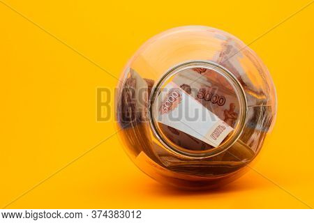 Five Thousandth Notes Are Packed In A Glass Jar Lying On Its Side