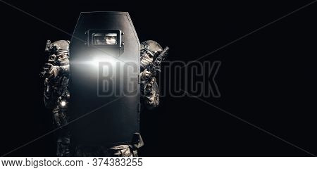 Portrait Of A Group Of Fighters Of A Special Unit. They Hide Behind A Bulletproof Shield. Black Back