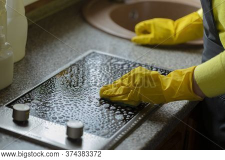 Hands In Yellow Gloves Wipe Surface Of Black Induction Stove House Cleaning Concept. Household Chemi
