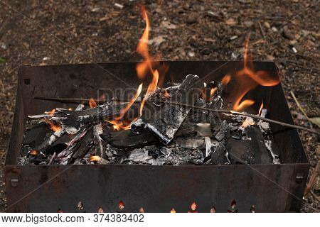 Metal Portable Barbecue On The Ground In The Yard. Firewood Burns Out In The Barbecue, A Bright Oran