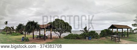 Kauai - April 6, 2018: Picnic Benchs Surrounded By Trees Along Rocky Shore With Naupaka Plant Leadin