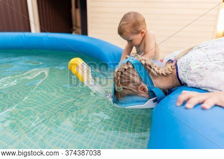 Cute Adorable Caucasian Blond Little Girl Making Experiment Try Diving In Pool With Full Face Snorke