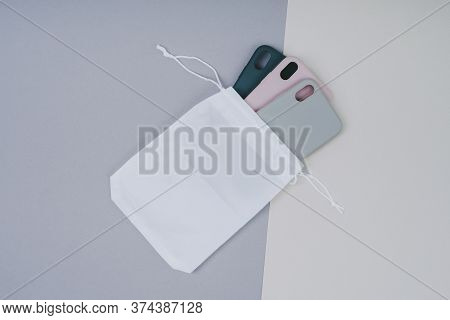 A Set Of Smartphone Cases In A White Eco-bag. Silicone Cases On A Gray Background.