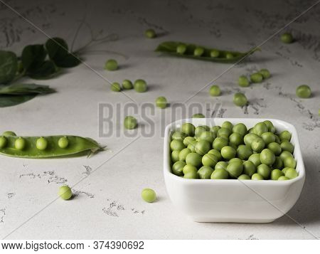 The Fruits And Pods Of Green Peas On A Gray Background.