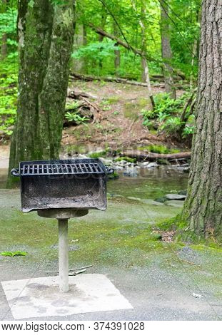 Vertical Shot Of A Heavily Used Grill At A Picnic Area With Trees And A Stream Behind It.