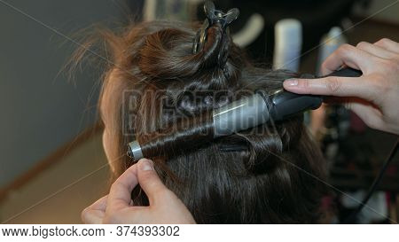 The Hairdresser Curls The Hair Of A Girl In A Beauty Salon Using A Curling Iron.