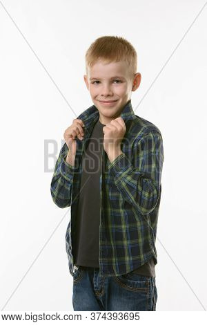 Blond Boy On A White Background Holds Hands Behind The Collar Of A Checkered Shirt