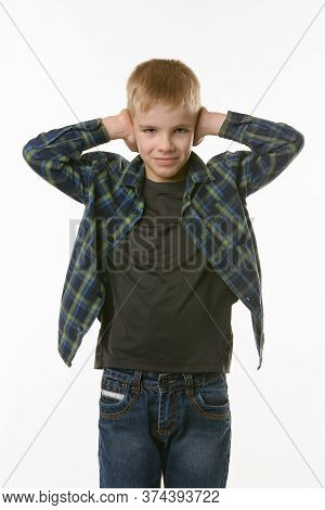 Boy Covers His Ears With His Hands On A White Background In Everyday Clothes