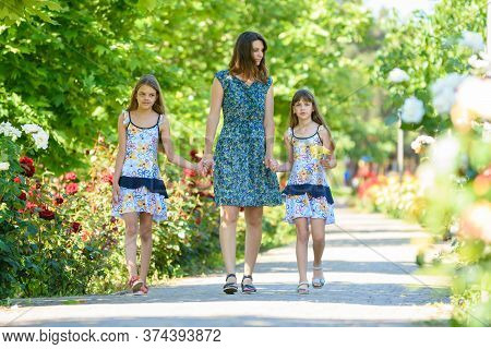 Young Woman Walks Down The Path In The Flowering Garden By The Hand With Her Two Daughters
