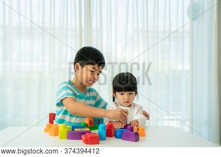 Asian Cute Brother And Sister Play With A Toy Block Designer On The Table In Living Room At Home. Co