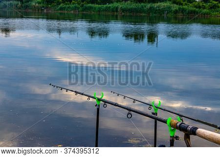 Two Fishing Rods Are Held In Fishing Rod Holders. Carp Fishing Rods, Fishing Lines, Reels. The Conce