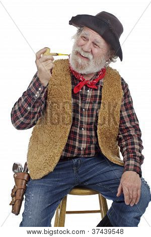 Cheerful Old Cowboy Sits With Holding Cob Pipe.