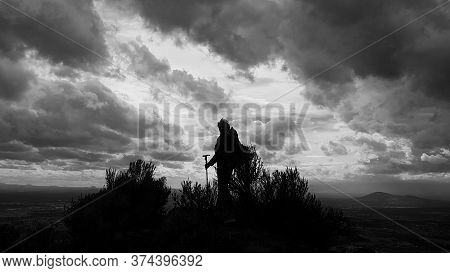 A Hiker Stands On The Summit Of Smith Rock In Oregon As A Storm Brews.