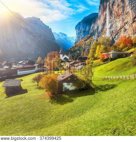 Gorgeous Autumn Landscape Of  Alpine Village Lauterbrunnen With Famous Church And Staubbach Waterfal