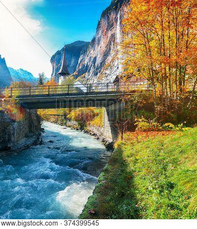 Amazing Autumn Landscape Of Touristic Alpine Village Lauterbrunnen With Famous Church And Staubbach