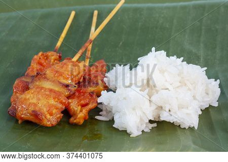 Grilled Pork With Sticky Rice On Banana Leaf Background Is A Food That Thai People Prefer To Eat.