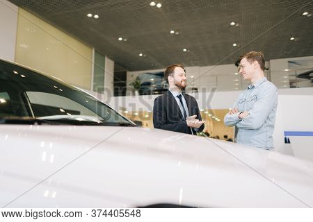 Happy Smiling Customer And Friendly Salesman Wearing Business Suit Are Discussing New Car In Auto De