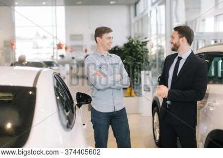 Cheerful Happy Man Preparing To Buy New Car In Auto Dealership. Professional Car Salesman Is Telling