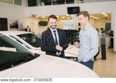 Professional Car Salesman Wearing Business Suit Is Telling Interested Buyer About Car In Auto Showro