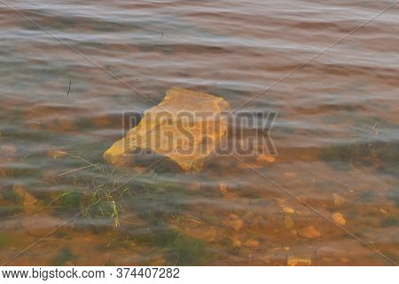 Green Algae, A Large Boulder And Small Stones Under Muddy Water Against The Background Of The Visibl