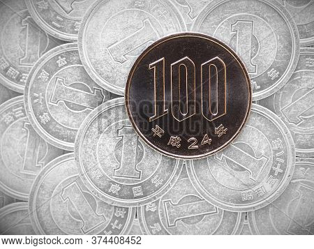 100 One Hundred Yen Lie On A Field Of Japanese Coins At 1 Yen. News About The Economy, Finance And T