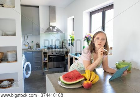 Shocked Young Woman Using Tablet Near Saucepan On Counter While Cooking In Her Kitchen, Leaning On T