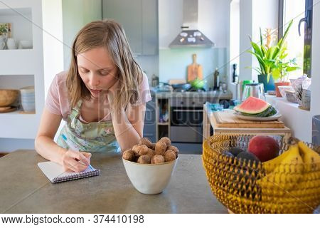 Focused Housewife Planning Weekly Menu In Her Kitchen, Writing Down Grocery List In Notebook. Cookin
