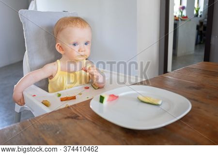 Pensive Sweet Baby Girl Trying Piece Of Watermelon While Sitting In Highchair With Food Messy On Tra