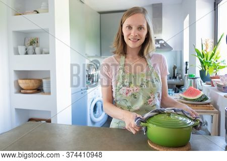 Positive Housewife Cooking In Her Kitchen, Holding Hot Saucepan With Towel, Looking At Camera And Sm