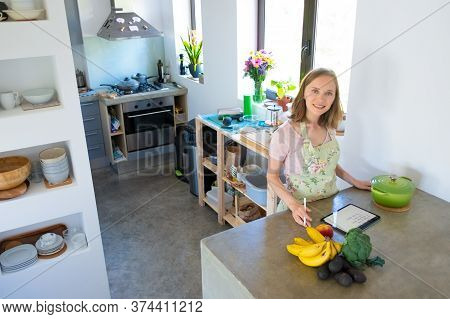 Happy Woman Consulting Recipe On Pad While Cooking In Her Kitchen, Using Tablet Near Saucepan And Fr