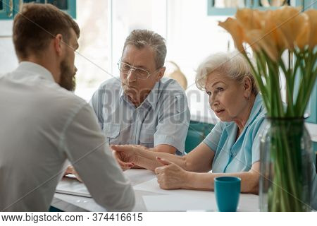 Elderly Couple Consults A Real Estate Agent About House Sale