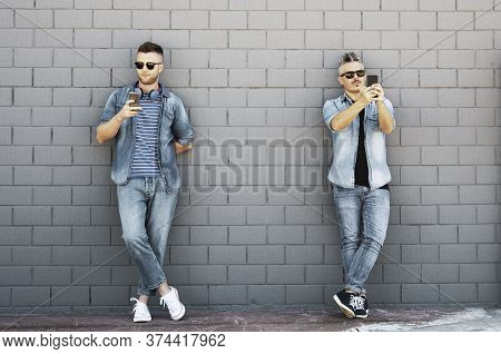 Two Young Man Looking At Mobile Phone Lean Against Brick Wall - Couple Of Cool Guys Using Smartphone