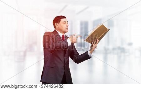 Senior Businessman Finger Pointing Into Open Book. Portrait Of Adult Man In Business Suit And Tie St