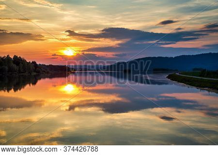 Mirroring Of The Landscape At Sunset On The Water Surface Of The Dam. Zilina Dam In The North Of Slo