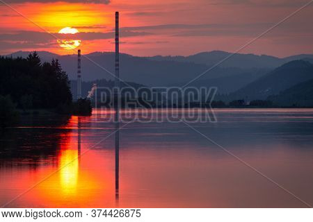 Industrial Landscape With Chimney Constructions Reflected On The Water Surface Of The Dam At Sunset.