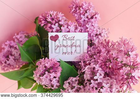 Inscription Best Grandma Ever On A White Gift Card In A Beautiful Spring Bouquet Of Lilac Flowers