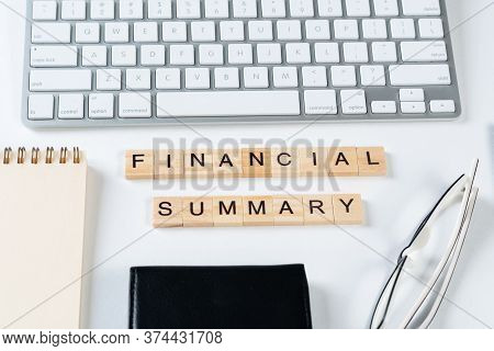Financial Summary Concept With Letters On Wooden Cubes. Still Life Of Office Workplace With Supplies