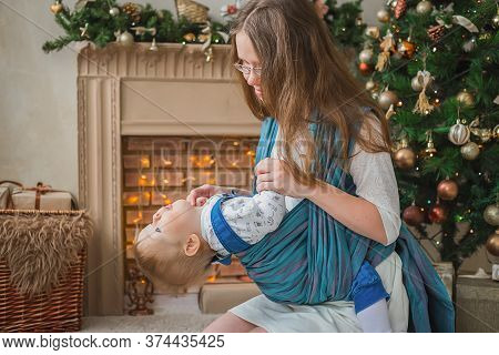 Portrait Of Young Mother Carrying Baby Son In Sling Against Christmas Interior In Bright Room At Hom