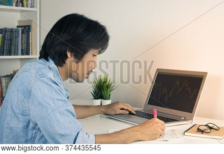 Asian Forex Trader Or Investor Or Businessman Wear Jean Shirt Writing Financial Report And Trading F