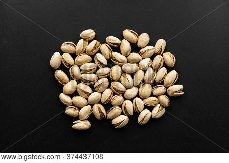 Pistachios Scattered On A Black Table. Pistachio Is A Healthy Vegetarian Protein Nutritious Food. Na
