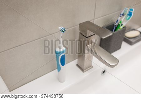 An Electric Toothbrush And An Old Toothbrush Near The Washbasin.