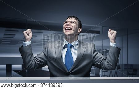 Happy Excited Businessman Celebrating Victory In Business. Businessman Feeling Satisfaction From Win